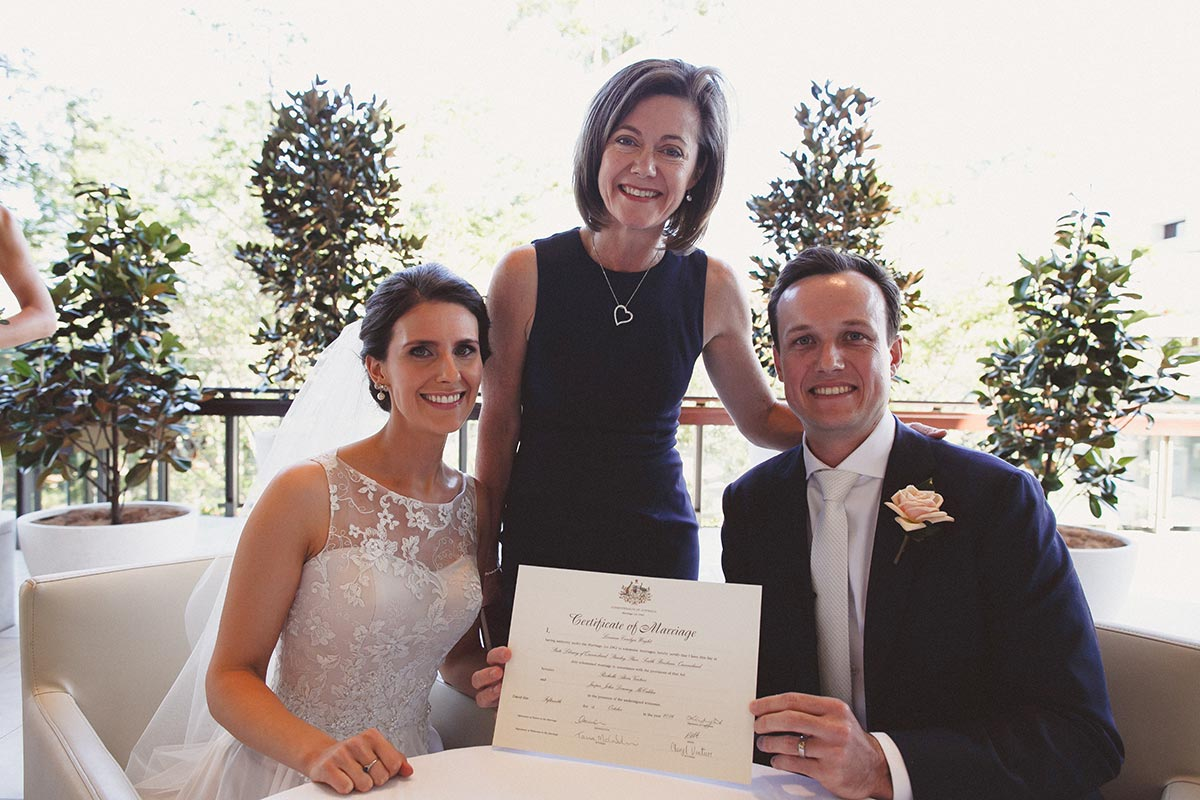 Wedding Celebrant Lorraine Wright with bride and groom who are sitting at the registry table holding their marriage certificate at the Queensland State Library
