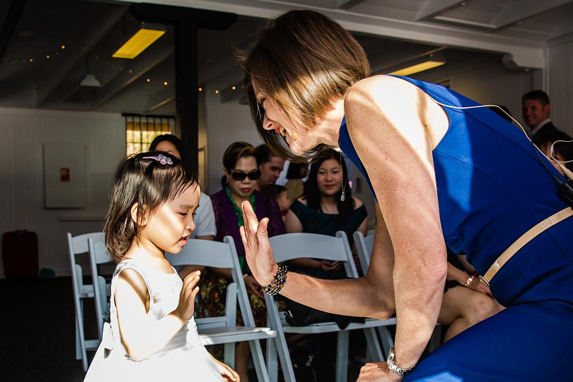 Marriage Celebrant Lorraine Wright wears a cobalt blue dress and leans forward to high-five a young flower girl at a wedding at Riverlife Brisbane