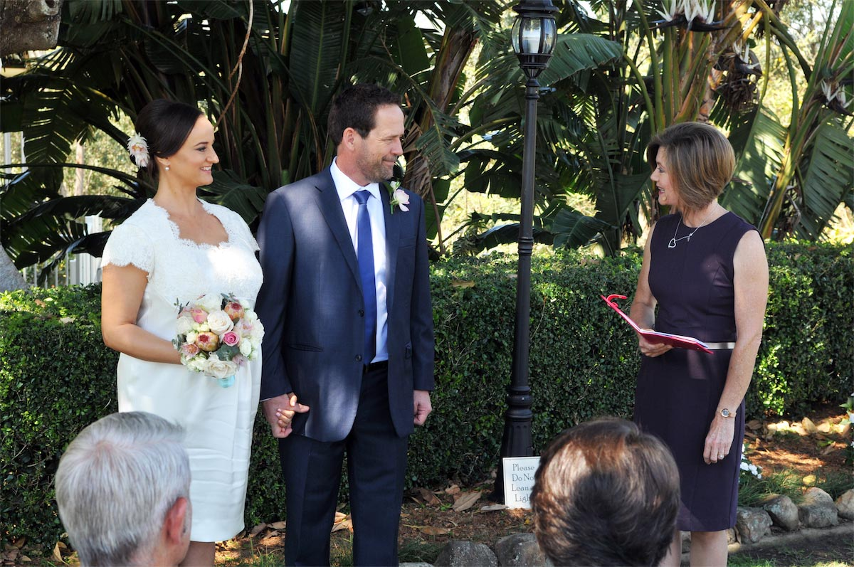 Female celebrant Lorraine Wright wearing a fitted plum Cue dress and speaking to the bride and groom during a wedding at Topiaries at Samford
