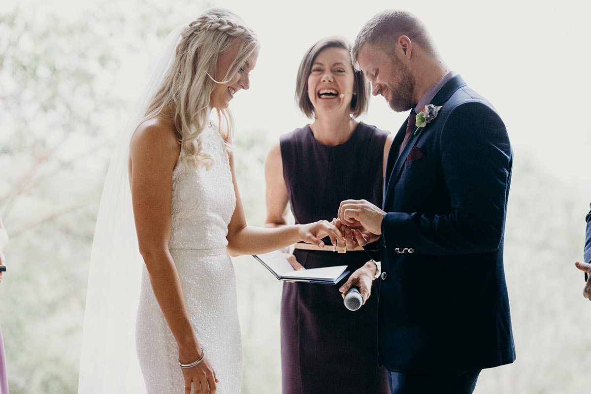 Marriage Celebrant Lorraine Wright laughing as groom makes a joke and places ring on bride's finger at Clear Mountain Lodge Wedding