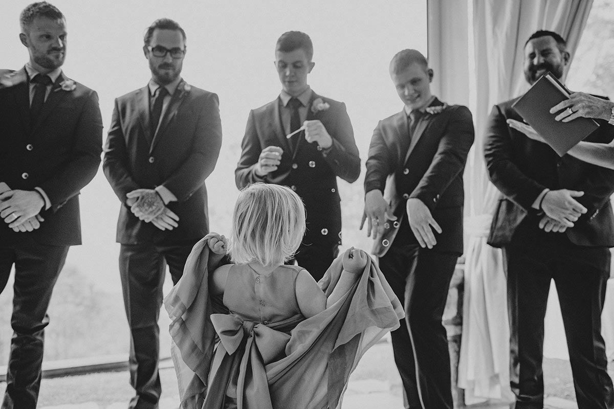 Toddler flower girl lifts her dress as she dances in front of the groomsmen at a Clear Mountain Lodge Wedding