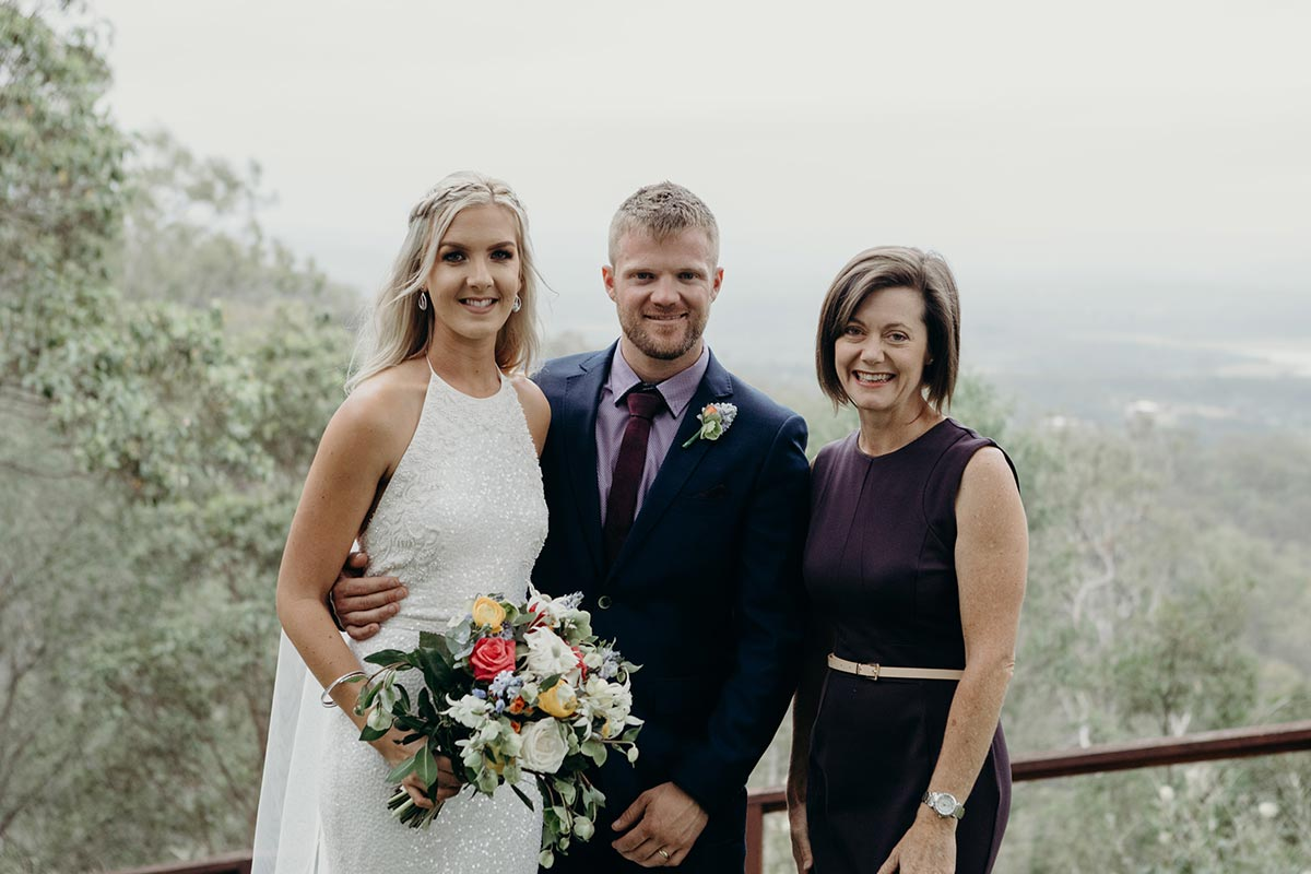 Wedding Celebrant Lorraine Wright standing with smiling bride and groom as bride holds her colourful  bouquet after their wedding at Clear Mountain Lodge
