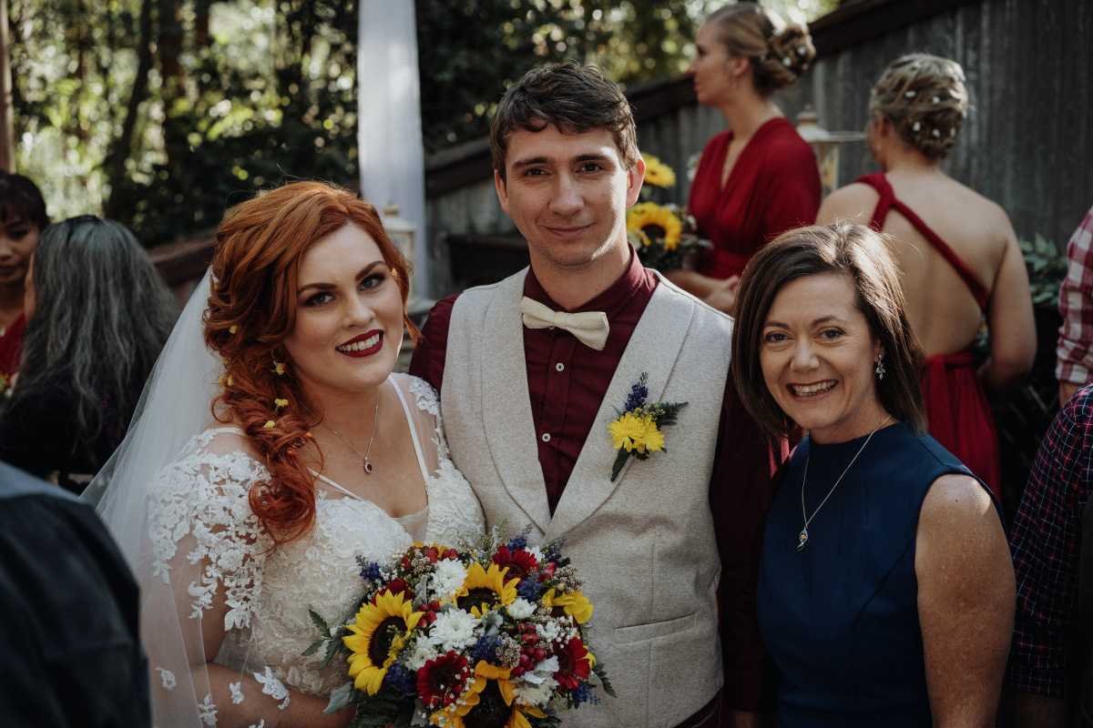 Marriage Celebrant Lorraine Wright with smiling groom and bride holding a bright bouquet after a wedding at Walkabout Creek