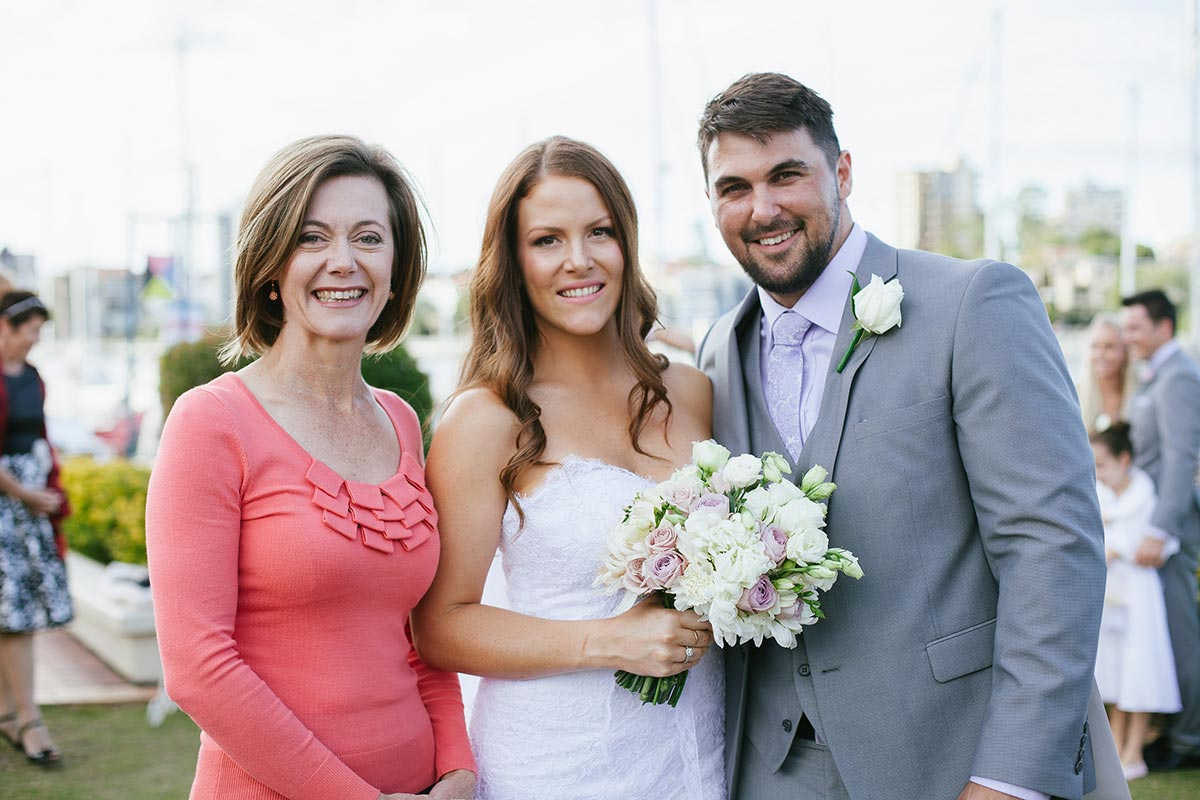 Marriage Celebrant Lorraine Wright wearing coral long sleeved top and standing with smiling bride and groom with city skyline and Brisbane River in the background as bride holds her pale  bouquet after their wedding at The Landing at Dockside