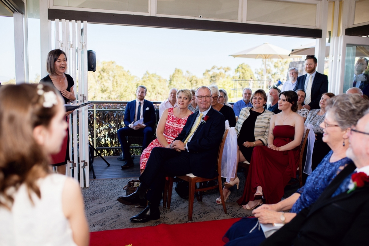 Female celebrant Lorraine Wright laughing with wedding guests as she prepares them for the ceremony which is about to start at The Summit Restaurant at Mount Coot-tha