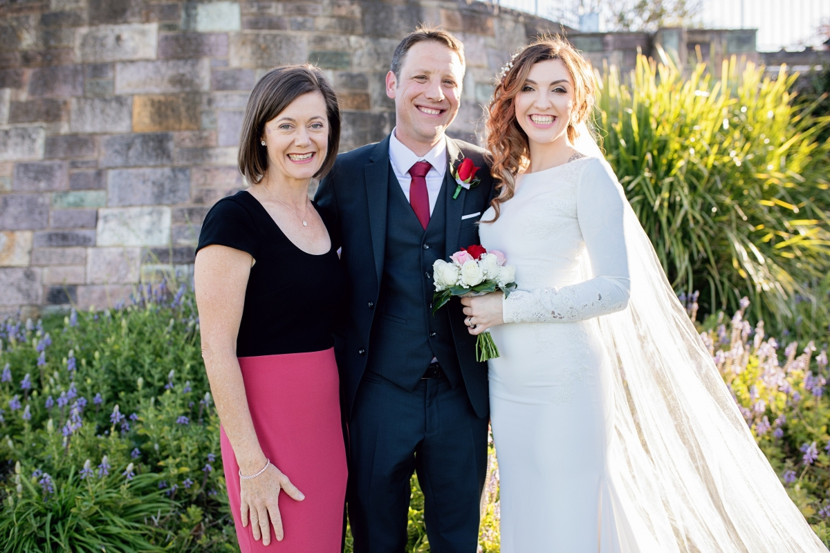 Lorraine Wright Marriage Celebrant wearing a black and coral Portmans dress and standing with bride and groom in front of a garden and brick wall at The Summit at Mount Coot-tha