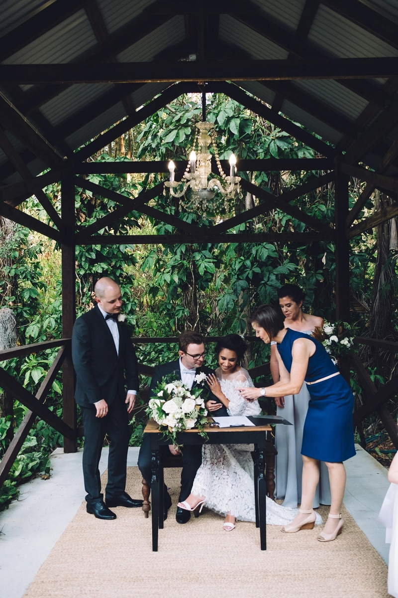 Marriage Celebrant Lorraine Wright wearing a cobalt blue Cue dress and showing bride and groom where to sign their marriage certificate as they sit at the registry table in an outdoor chapel at their Rainforest Gardens wedding at Mount Cotton