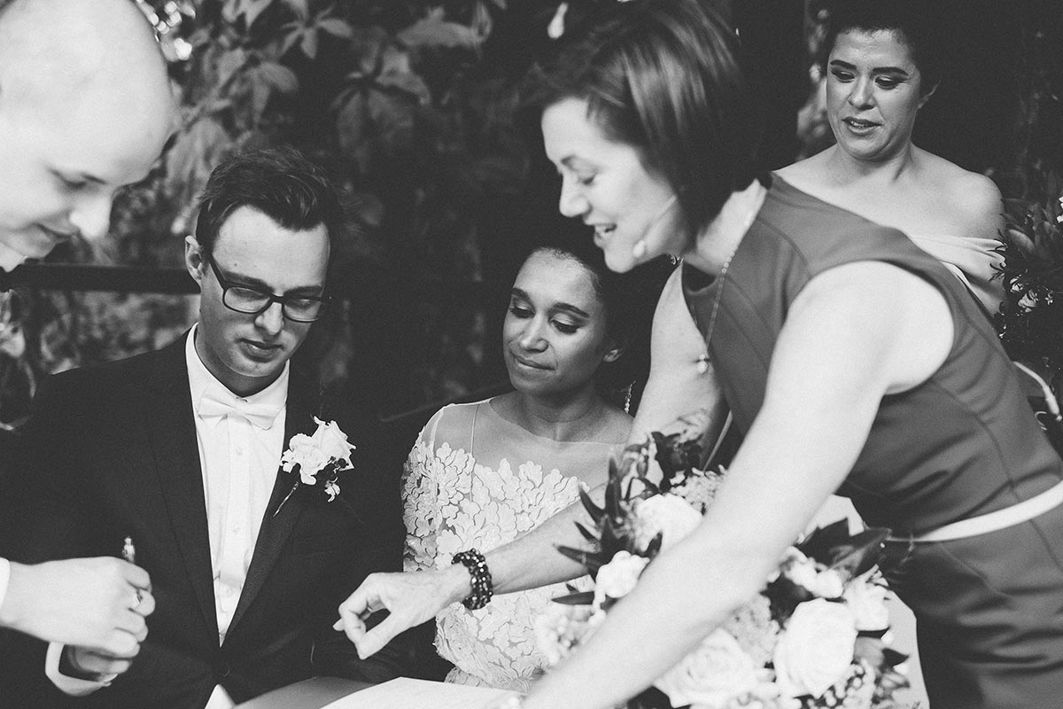 Wedding Celebrant Lorraine Wright leaning over to show bride and groom where to sign their marriage certificate as they sit at the registry table in an outdoor chapel at their Rainforest Gardens wedding at Mount Cotton