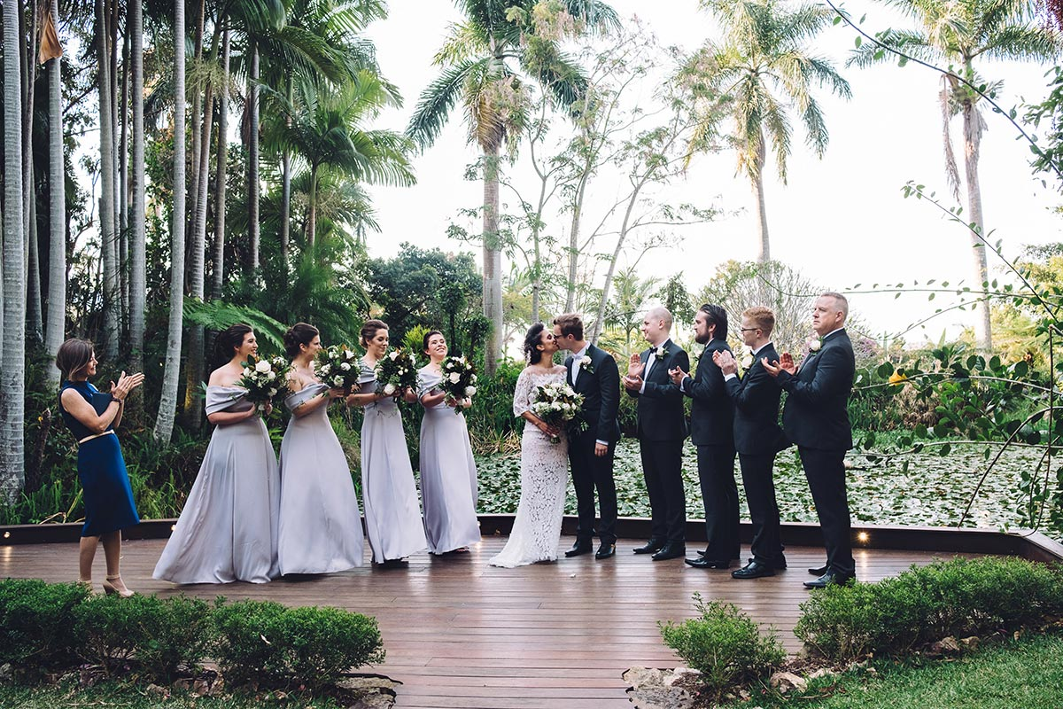 Experienced celebrant Lorraine Wright stands beside bridal party and asks everyone to clap for the newlyweds at their Rainforest Gardens wedding at Mount Cotton