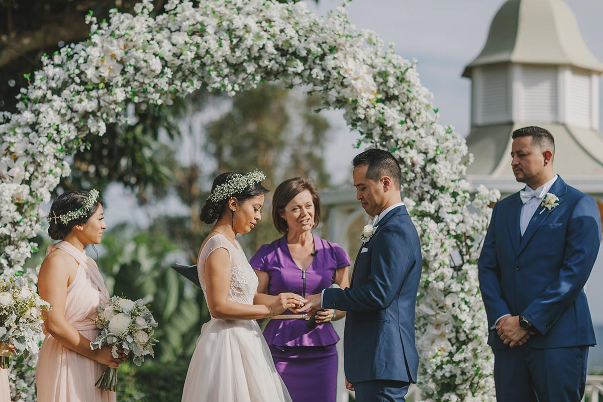 Celebrant Lorraine Wright wearing a purple dress and standing with bride and groom in front of a white floral arched arbor at a garden wedding at Topiaries at Samford