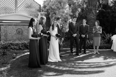 Marriage Celebrant Lorraine Wright standing beside bridal party and speaking as bride smiles at the camera