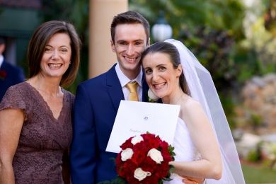 Wedding Celebrant Lorraine Wright with smiling bride and groom in the garden at The Golden Ox as bride holds bouquet and marriage certificate
