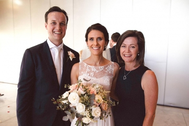 Wedding Celebrant Lorraine Wright standing with smiling bride and groom as bride holds her pale bridal bouquet after wedding at the State Library of Queensland