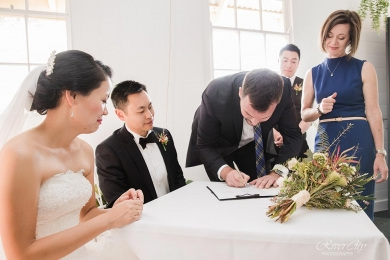 Wedding Celebrant Lorraine Wright wears a cobalt blue dress and stand beside registry table where a witness is bending down to sign the marriage certificate next to seated bride and groom