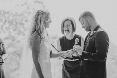 Celebrant Lorraine Wright laughing as groom says funny vows and places ring on bride's finger at Clear Mountain Lodge Wedding