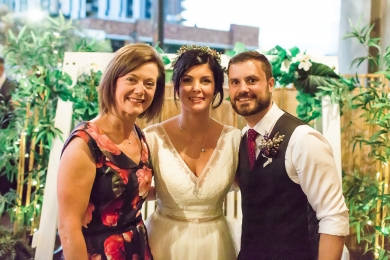 Female Celebrant Lorraine Wright with smiling bride and groom standing on the deck at Loft West End