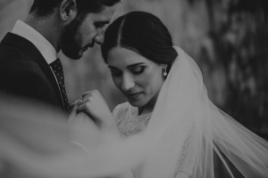 bride wearing a white veil looking down while groom looks lovingly down at her