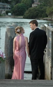 Bride wearing pale pink bias-cut wedding dress and groom wearing dark suit standing on a jetty