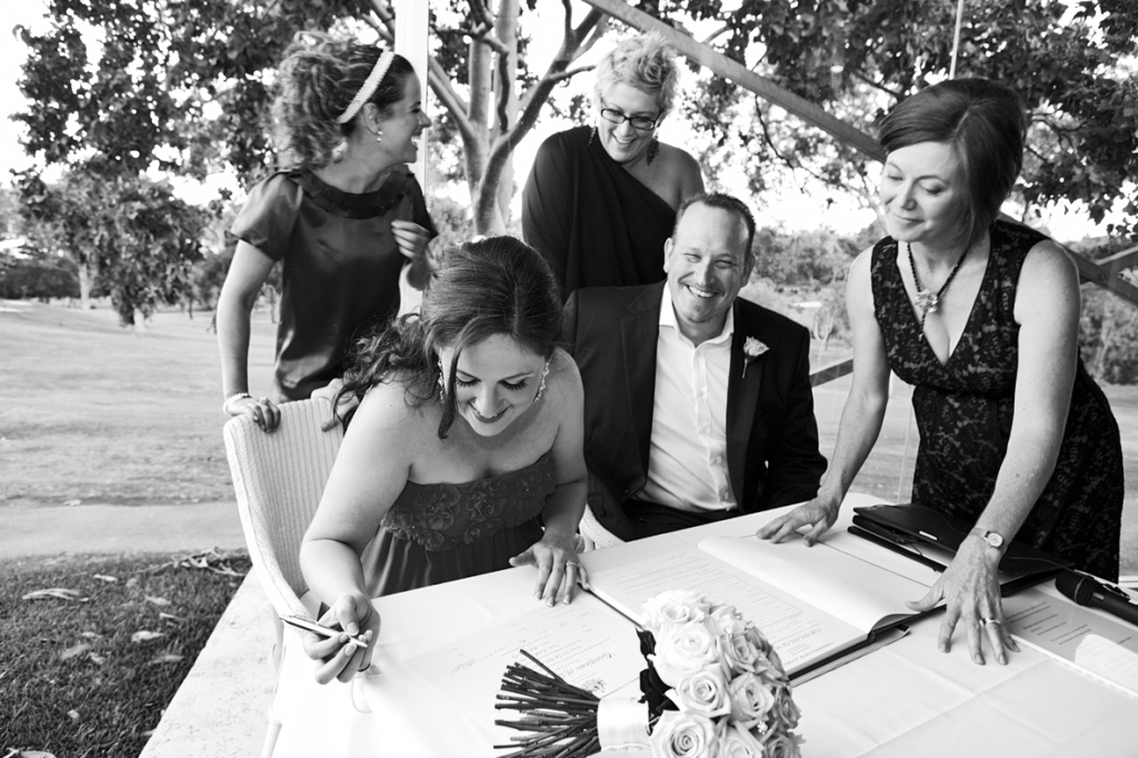 Bride and Groom signing the marriage register and celebrant showing them where to sign