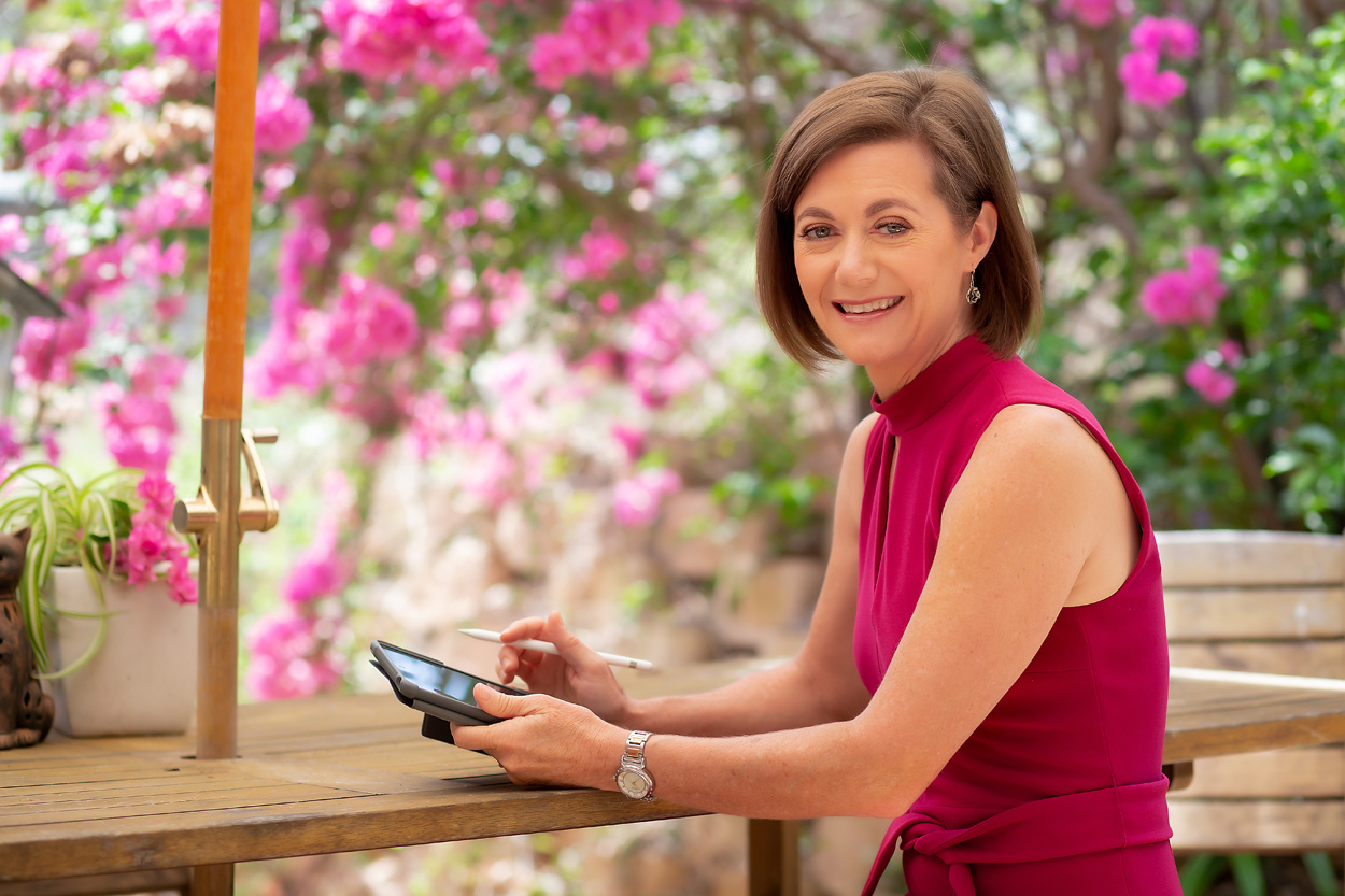 Lorraine Wright wearing a cerise Portmans sleeveless dress sitting at a wooden picnic table in a garden surrounded by pink Bougainvillea flowers holding an ipad and pen and smiling at the camera