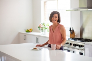 Lorraine Wright wearing a dusky pink top standing behind a white counter holding a pink coffee mug in a neutral kitchen with pale pink flowers and a fruit bowl in the background and a plate of cookies on the bench