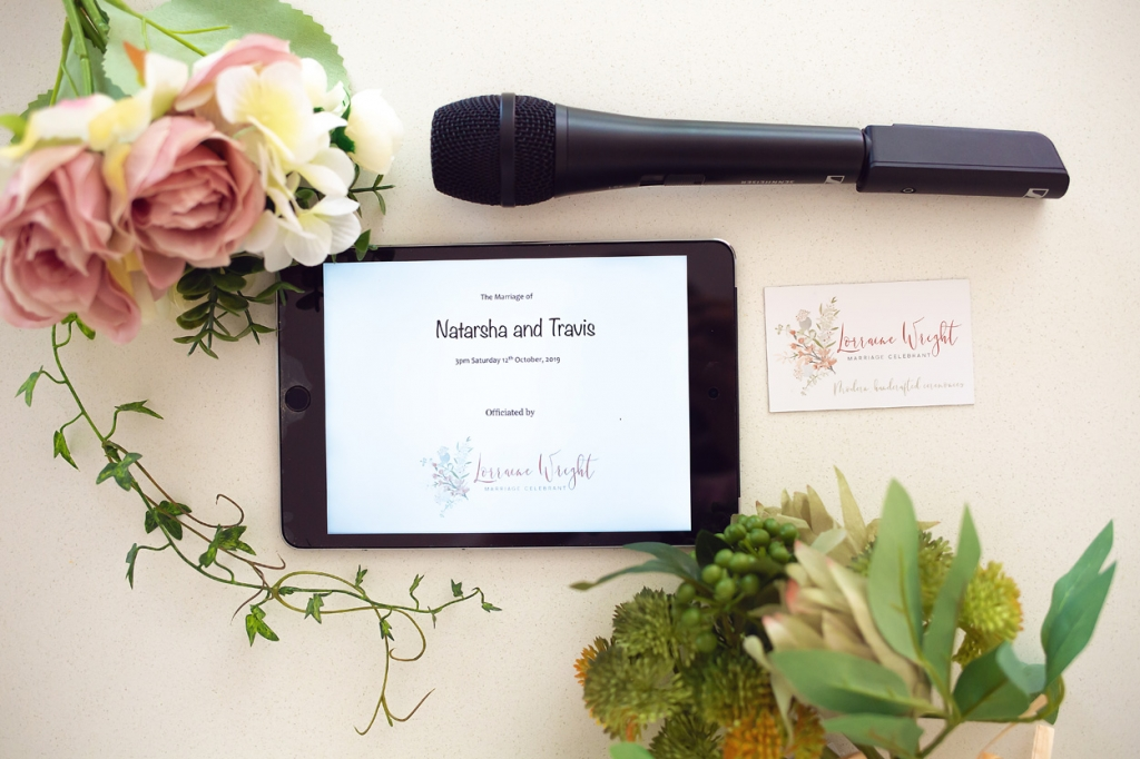 Microphone and ipad with flowers and business card on a white background ready for a wedding ceremony with Lorraine Wright as the celebrant