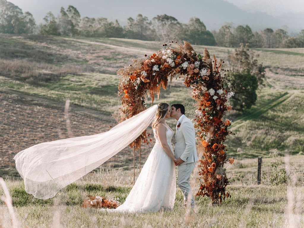 Bridal and groom kissing in front of a floral arbour on a hillside