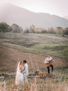 Bride and groom dance in the paddock as guitarist plays