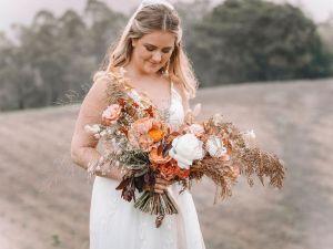 Bride carries a rustic bouquet as she walks to her elopement ceremony on a farm